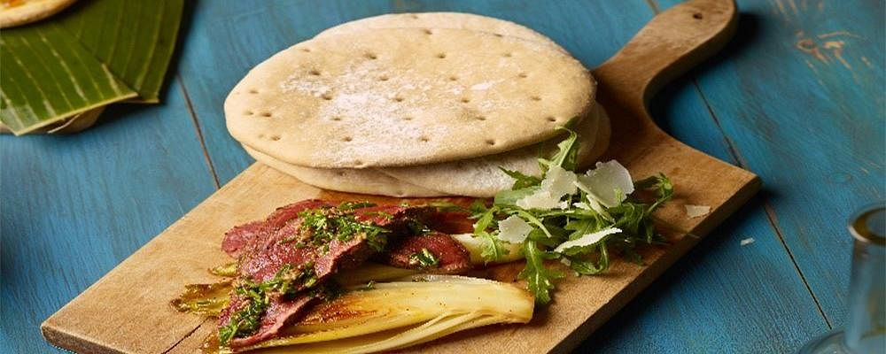 Recipe: Griddled Sourdough Flatbreads with Truffle butter, Caramelized Chicory, Seared Pink Peppered Beef & Chive and Mustard Dressing.